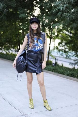 Cómo combinar: camiseta sin manga estampada negra, minifalda de cuero negra, botines de cuero con print de serpiente amarillos, bolso bandolera de cuero negro