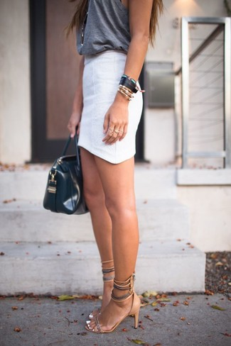 Cómo combinar: camiseta sin manga en gris oscuro, minifalda blanca, sandalias de tacón de ante marrón claro, bolsa tote de cuero negra