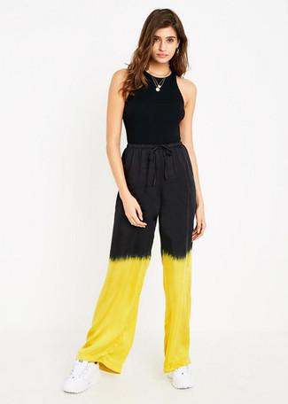 Cómo combinar: camiseta sin manga negra, pantalones anchos efecto teñido anudado amarillos, deportivas blancas, colgante dorado