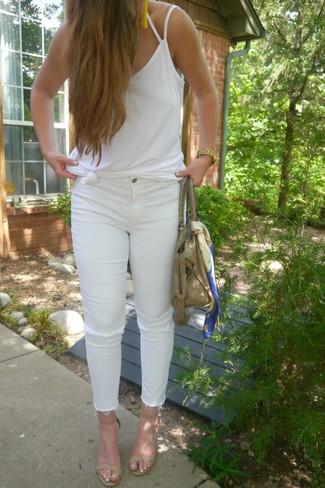 Cómo combinar: camiseta sin manga blanca, vaqueros pitillo desgastados blancos, sandalias de tacón de cuero en beige, bolsa tote de cuero en beige
