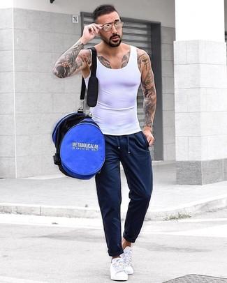 Cómo combinar: camiseta sin mangas blanca, pantalón de chándal azul marino, tenis blancos, bolso baúl azul