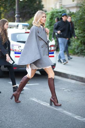 Cómo combinar: capa gris, vestido recto de encaje blanco, botas de caña alta de cuero burdeos