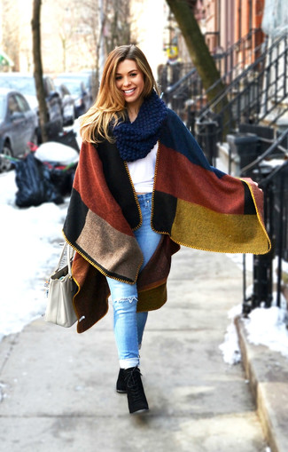 Effortlessly blurring the line between chic and casual, this combination of a multi colored cape coat and light blue distressed skinny jeans is likely to become one of your favorites. For the maximum chicness grab a pair of black suede lace-up ankle boots.