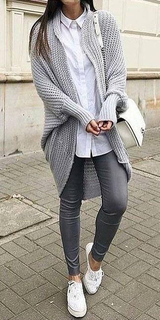 Cómo combinar: cárdigan abierto de punto gris, camisa de vestir blanca, pantalones pitillo de cuero grises, tenis de cuero blancos