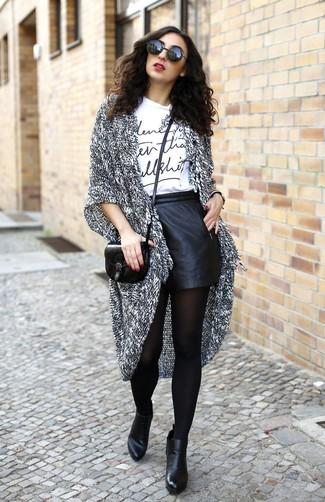 Cómo combinar: cárdigan abierto de punto gris, camiseta con cuello circular estampada en blanco y negro, pantalones cortos de cuero negros, botines de cuero negros