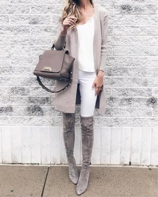 Cómo combinar: cárdigan abierto en beige, camiseta sin manga de satén blanca, vaqueros pitillo blancos, botas sobre la rodilla de ante grises