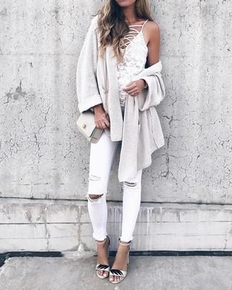 Cómo combinar: cárdigan abierto de punto en beige, camiseta sin manga de encaje blanca, vaqueros pitillo desgastados blancos, sandalias de tacón de cuero blancas