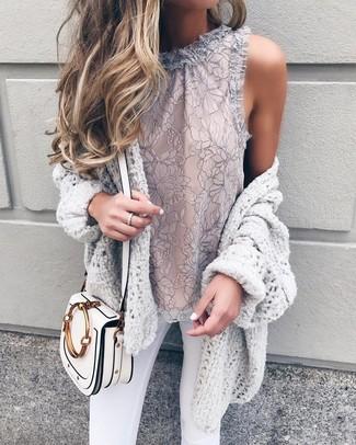 Cómo combinar: cárdigan abierto de punto gris, blusa sin mangas de encaje gris, vaqueros pitillo blancos, bolso bandolera de cuero blanco