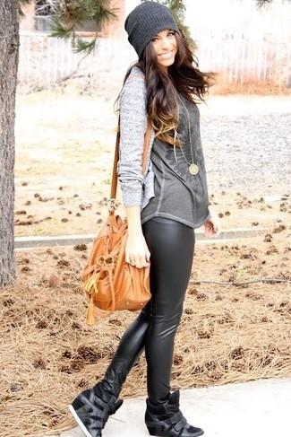 Cómo combinar: cárdigan gris, camiseta con cuello circular estampada en gris oscuro, leggings de cuero negros, zapatillas con cuña de cuero negras
