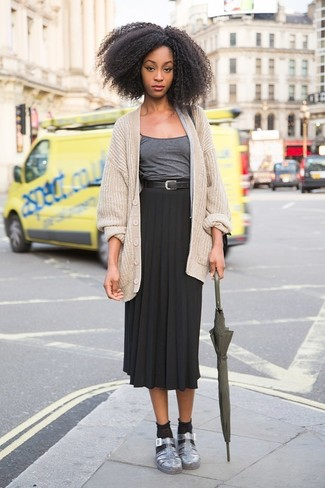 Cómo combinar: cárdigan de punto en beige, camiseta sin manga en gris oscuro, falda midi plisada negra, sandalias planas de cuero plateadas