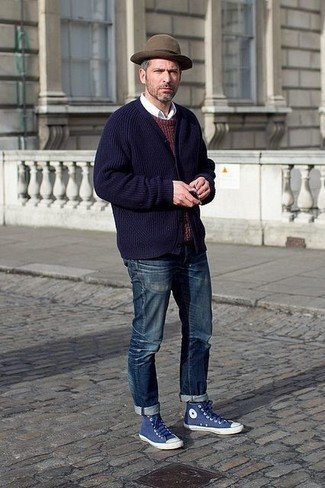 How to Wear Navy Canvas High Top Sneakers For Men: A navy cardigan and navy jeans are a great combination worth integrating into your day-to-day fashion mix. A good pair of navy canvas high top sneakers is an easy way to infuse a touch of stylish casualness into this look.