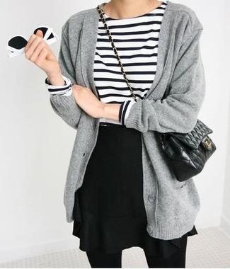 Cómo combinar: cárdigan grueso gris, camiseta de manga larga de rayas horizontales en blanco y negro, falda skater negra, bolso bandolera de cuero acolchado negro