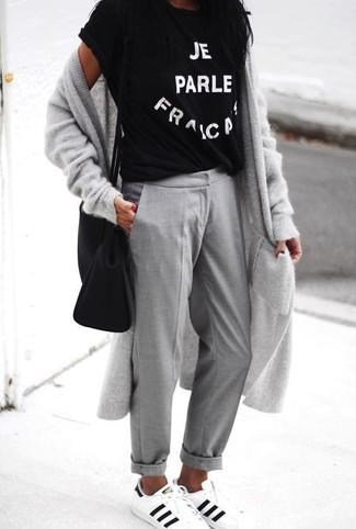 Cómo combinar: cárdigan largo gris, camiseta con cuello circular estampada en negro y blanco, pantalón chino gris, tenis de cuero en blanco y negro