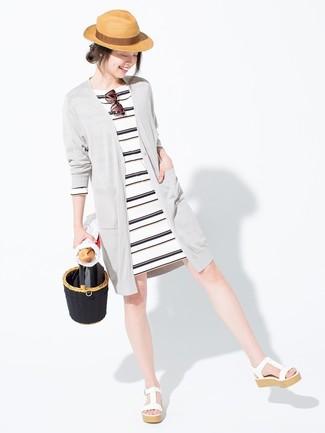 Cómo combinar: cárdigan largo gris, vestido casual de rayas horizontales en blanco y negro, sandalias con cuña de cuero blancas, sombrero de paja marrón claro