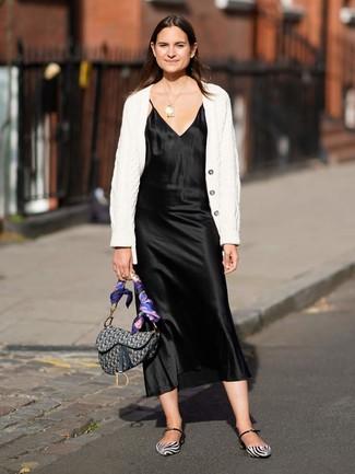 Cómo combinar: cárdigan de punto blanco, vestido camisola de satén negro, bailarinas de cuero en blanco y negro, bolso de hombre de lona estampado gris