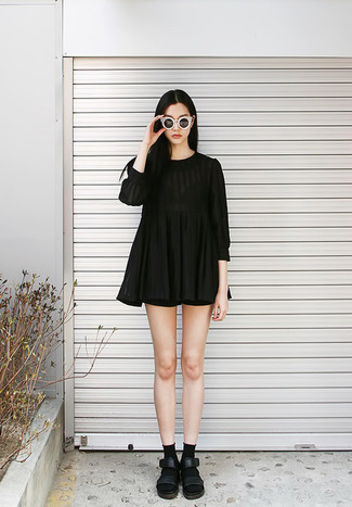 Team a black pleated casual dress with black shorts to effortlessly deal with whatever this day throws at you. Black leather flat sandals will give your look an on-trend feel.