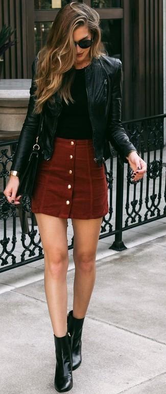 Cómo combinar: cazadora de aviador de cuero negra, camiseta con cuello circular negra, falda con botones de ante roja, botines de cuero negros