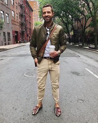 Cómo combinar: cazadora de aviador verde oliva, camiseta con cuello circular gris, pantalón chino marrón claro, zapatillas slip-on de lona estampadas en multicolor