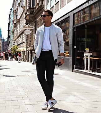 Cómo combinar: cazadora de aviador gris, camiseta con cuello circular blanca, pantalón chino negro, tenis de cuero estampados blancos