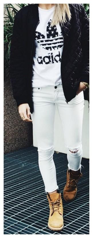 Cómo combinar: cazadora de aviador acolchada negra, camiseta con cuello circular estampada en blanco y negro, vaqueros pitillo desgastados blancos, botas planas con cordones de nubuck marrón claro