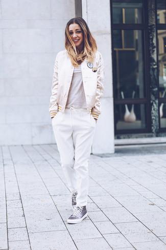 Cómo combinar: cazadora de aviador de satén en beige, camiseta con cuello circular gris, pantalón de pinzas blanco, zapatillas altas de lona grises