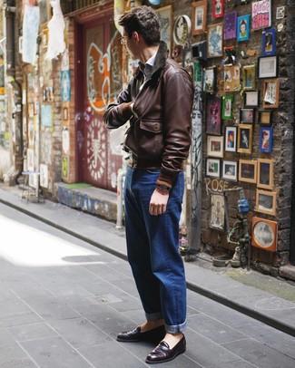 Cómo combinar: cazadora de aviador de cuero en marrón oscuro, camisa de manga larga celeste, vaqueros azules, mocasín de cuero morado oscuro