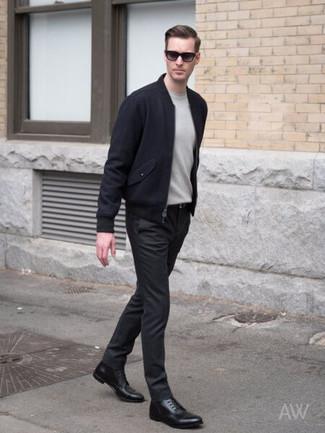 Cómo combinar: cazadora de aviador de lana azul marino, jersey con cuello circular gris, pantalón chino negro, botas formales de cuero negras