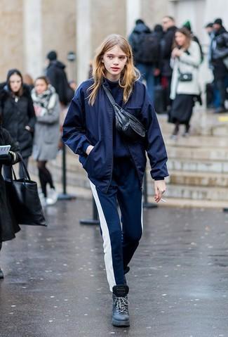 Cómo combinar: cazadora de aviador azul marino, jersey de cuello alto azul marino, pantalón de chándal en azul marino y blanco, botas planas con cordones de cuero negras