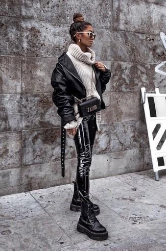 Cómo combinar: cazadora de aviador de cuero negra, jersey de cuello alto de lana de punto blanco, pantalones pitillo de cuero negros, botas planas con cordones de cuero gruesas negras