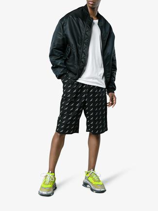 Cómo combinar: cazadora de aviador negra, camiseta con cuello circular blanca, pantalones cortos estampados en negro y blanco, deportivas en amarillo verdoso
