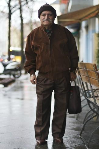Cómo combinar: cazadora de aviador de ante en marrón oscuro, pantalón de vestir de rayas verticales en marrón oscuro, botines chelsea de cuero en marrón oscuro, portafolio de lona negro