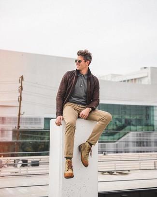 Cómo combinar: cazadora de aviador de cuero en marrón oscuro, polo de manga larga en gris oscuro, pantalón chino marrón claro, botas casual de lona marrón claro