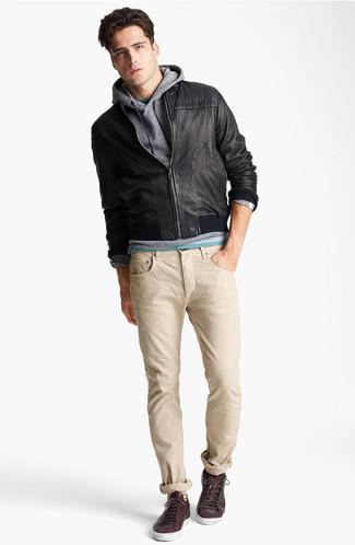 Cómo combinar: cazadora de aviador de cuero negra, sudadera con capucha gris, camiseta con cuello circular verde, vaqueros en beige