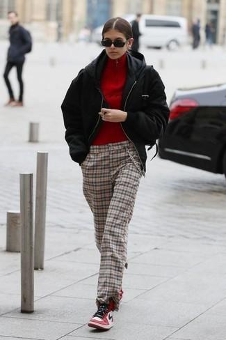 Cómo combinar: cazadora de aviador negra, sudadera con capucha negra, jersey de cuello alto con cremallera rojo, pantalones anchos a cuadros marrón claro