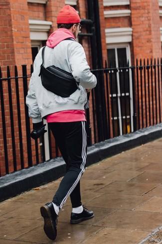 Cómo combinar: cazadora de aviador gris, sudadera con capucha rosa, pantalón de chándal de rayas verticales en negro y blanco, zapatos brogue de cuero negros