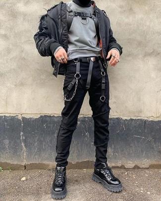 Cómo combinar: cazadora de aviador negra, sudadera gris, vaqueros pitillo desgastados negros, botas de trabajo de cuero negras