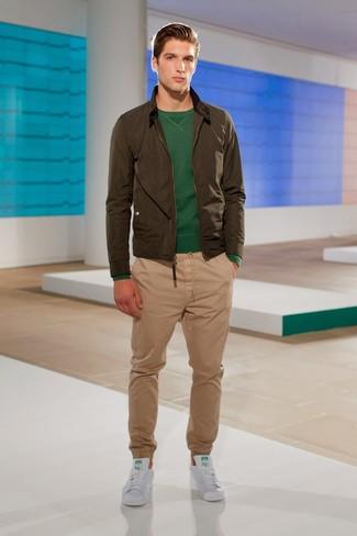 Cómo combinar: cazadora de aviador verde oliva, jersey con cuello circular verde oscuro, pantalón chino marrón claro, tenis de cuero blancos