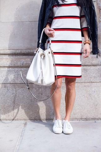 Cómo combinar: cazadora de aviador de cuero azul marino, vestido tubo de rayas horizontales en blanco y rojo, zapatillas plimsoll blancas, mochila con cordón de cuero blanca