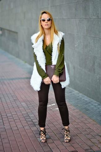 Cómo combinar: chaleco de pelo blanco, blusa de manga larga verde oliva, pantalones pitillo negros, sandalias de tacón de cuero con print de serpiente grises