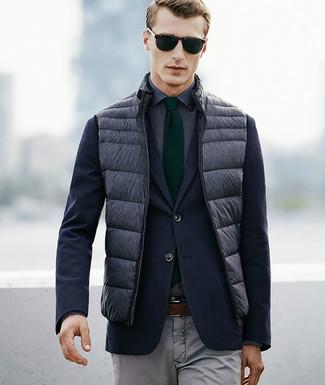 Cómo combinar: chaleco de abrigo acolchado gris, blazer azul marino, camisa de vestir a lunares en negro y blanco, pantalón chino gris