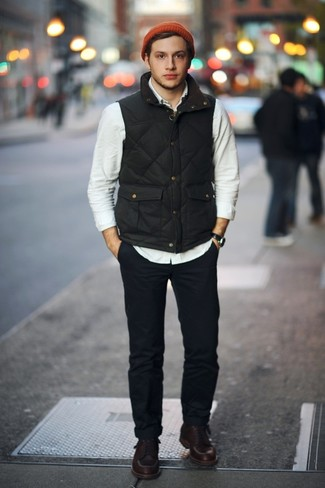 Cómo combinar: chaleco de abrigo negro, camisa de manga larga en beige, pantalón chino azul marino, botas de trabajo de cuero en marrón oscuro