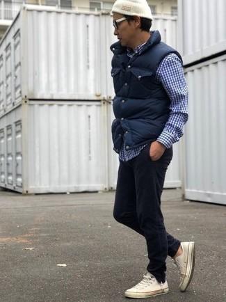 Cómo combinar: chaleco de abrigo acolchado azul marino, camisa de manga larga de cuadro vichy en azul marino y blanco, vaqueros de pana negros, tenis de lona blancos