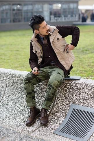 Cómo combinar: chaleco de abrigo en beige, cárdigan de punto en marrón oscuro, camisa vaquera azul, pantalón cargo de camuflaje verde oliva