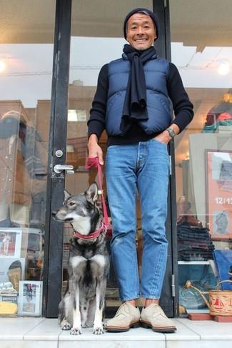Cómo combinar: chaleco de abrigo acolchado azul marino, jersey con cuello circular negro, vaqueros azules, zapatos derby de ante en beige