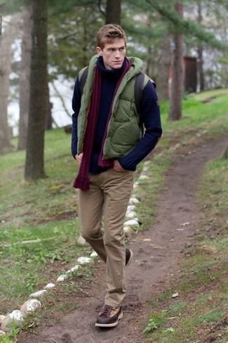Cómo combinar: chaleco de abrigo acolchado verde oliva, jersey de cuello alto de punto azul marino, pantalón chino marrón, botas casual de cuero en marrón oscuro