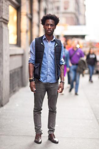 Cómo combinar: chaleco de abrigo negro, camisa de manga larga celeste, vaqueros grises, zapatos oxford de cuero marrónes
