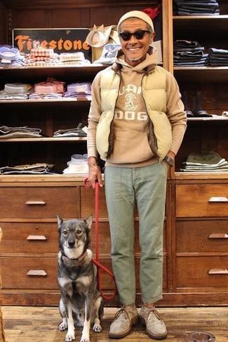 Cómo combinar: chaleco de abrigo acolchado en beige, sudadera con capucha estampada marrón claro, pantalón chino verde oliva, botas safari de ante grises