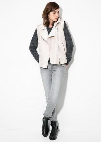 Cómo combinar: chaleco de piel de oveja en beige, jersey con cuello circular en gris oscuro, vaqueros pitillo grises, botines de cuero negros