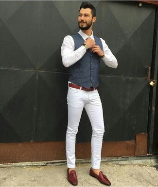 Cómo combinar: chaleco de vestir azul marino, camisa de vestir blanca, vaqueros pitillo blancos, mocasín con borlas de cuero marrón