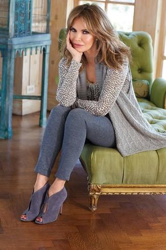 Cómo combinar: chaleco de punto gris, jersey con cuello circular de leopardo gris, leggings grises, botines de ante con recorte grises